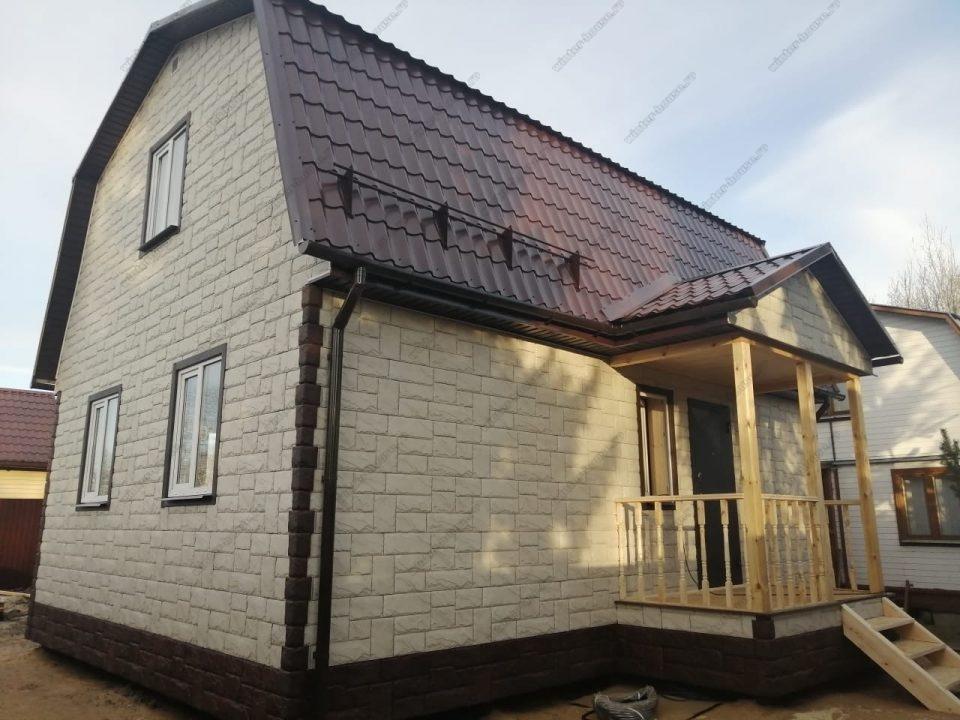 Фото каркасного дома с мансардой и террасой с отделкой панелями под кирпич
